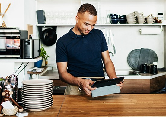 A barista using his digital tablet while working at the service counter in his cafe in the city.